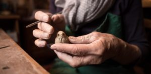 a pair of elderly hands carving a bird in clay